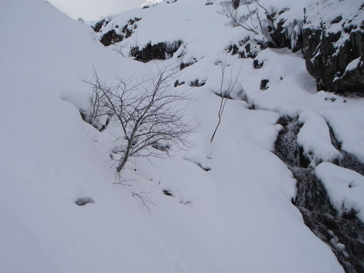 Heavy snow blanketing the blocks by the waterfall which the path takes.