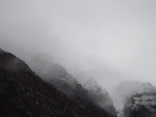 The turret-like buttresses of   the Aonach Eagach Ridge atmospheric looking in the cloud
