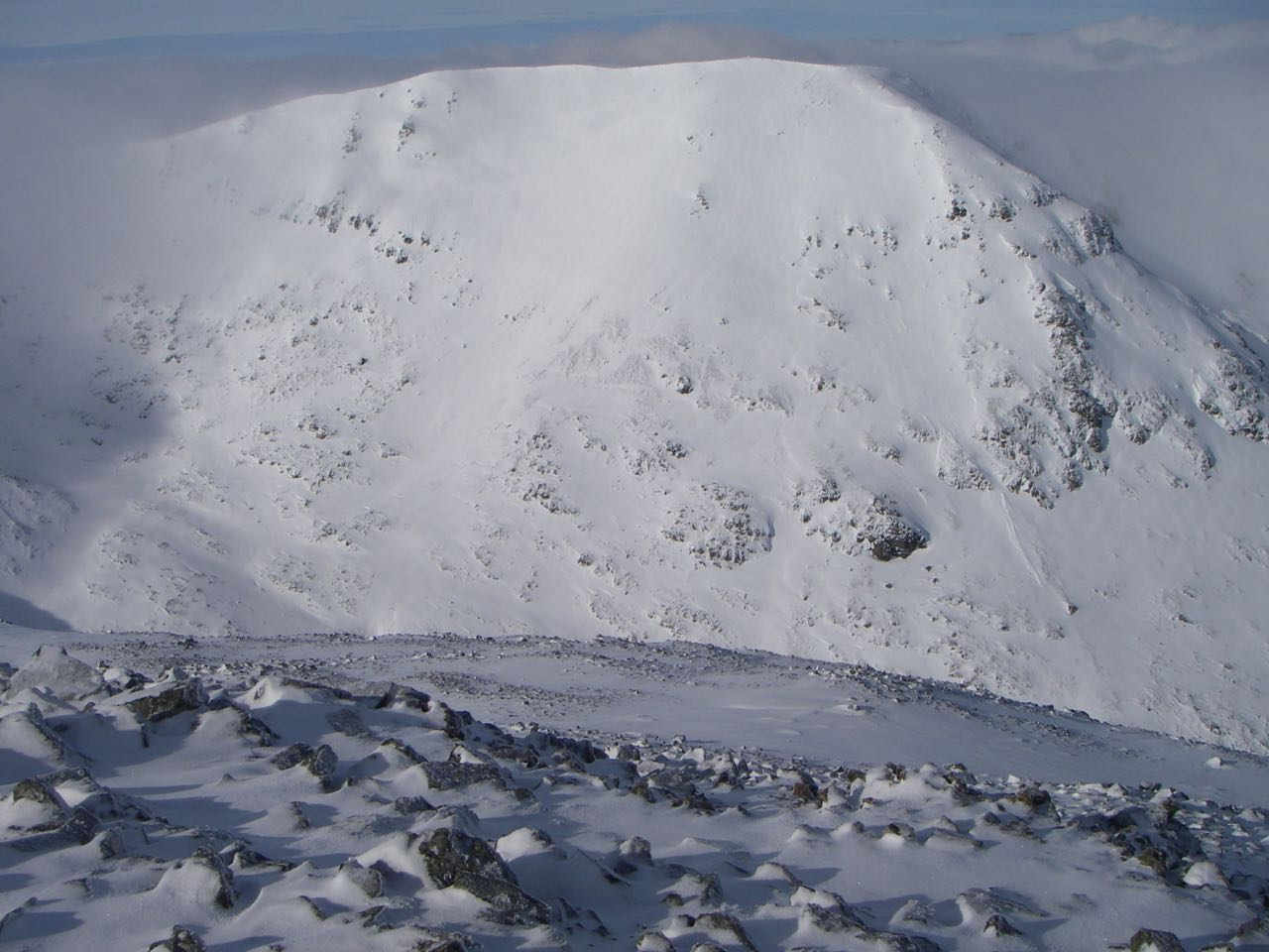Looking West from Meall a Bhuiridh contrasting its scoured West flank (near ground) with the loaded East face of Creise